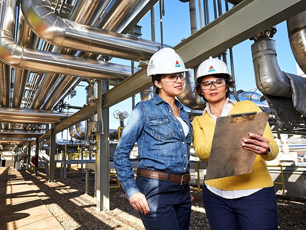 Women looking at clip board under electric plant piping