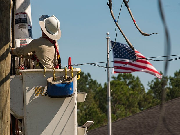 American flag in the background as a Georgia Power lineman makes repairs